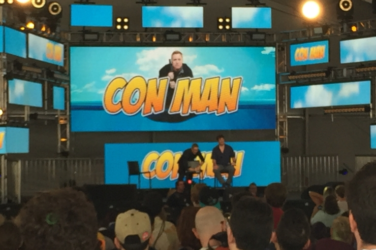 The cast of Con Man on stage answering fan questions